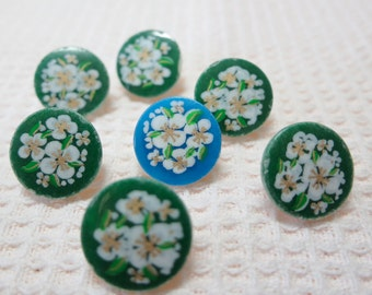 """7  buttons  with white flower, plastic.0.5"""" ins across.  6 matched white flowers with green,1 blue. LB12.5-6.24-1(A)"""
