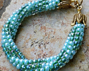 Beaded Kumihimo bracelet - green swirl with goldplate toggle
