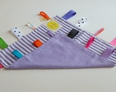 Baby Tag Blanket Made With Purple Fabrics And Bright Ribbons