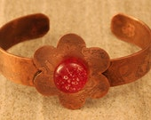 etched copper flower bracelet with fused glass centre