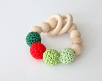 Red dot on shades of green. Teething ring toy with crochet wooden beads. Rattle for baby.