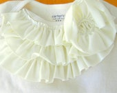 Ivory baby onesie with Ivory ruffles and long sleeves in size nb