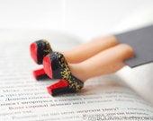 Louboutin bookmark covered with golden glitter. Legs in book. Elegant black high fashion gift.