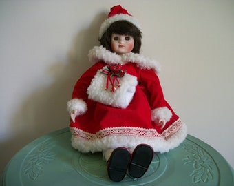 Porcelain doll child girl holiday red gold green winter velvet ribbon trim hat dress vintage figurine collectible