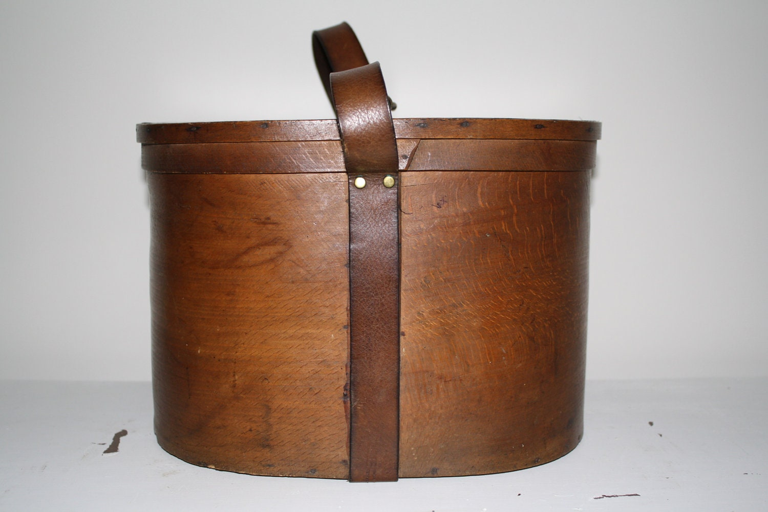 Antique English oval wood and leather strap hat box with