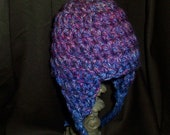 Earflap hat with yarn bow in shades of blue iris, pink and fushia..One of a kind