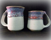 Two white mugs with mottled red & blue accents