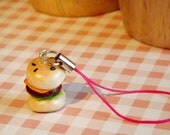 Polymer burger charm on a pink mobile phone lanyard.