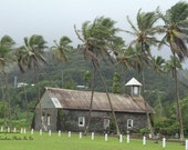 Ancient church on Maui, Hawaii with beautiful palm trees blowing. Volcanic mountains in background.
