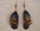 Three feathers together plus bicone glass beads. Pierced earrings are just over 4 inches in length.