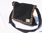 Black flip top messenger bag with red and tan flower inside
