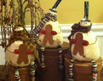 Primitive Shelf Sitting Snowman with bell and button dangle legs holding a gingerbread cookie