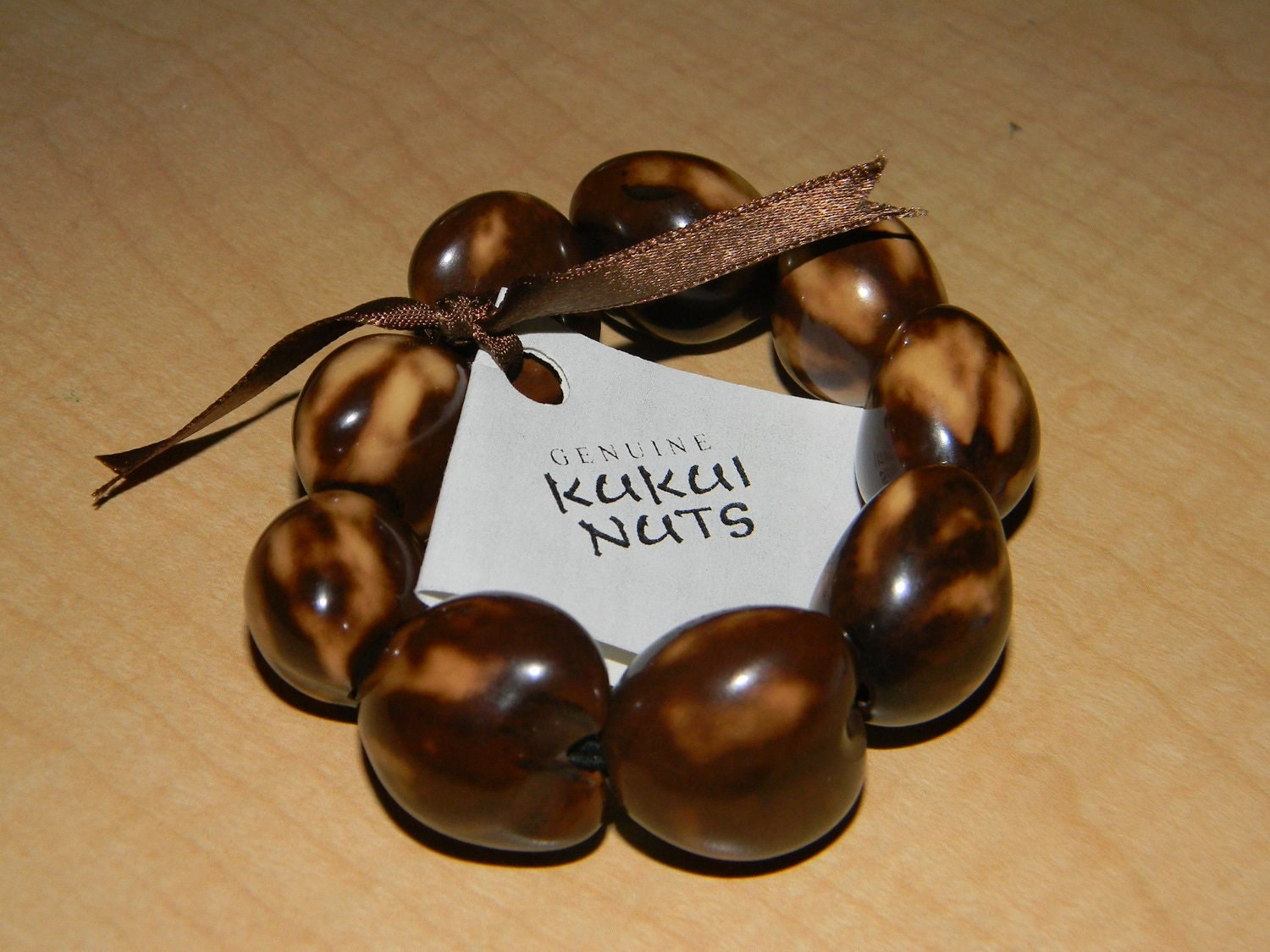 hawaiian kukui nut bracelet with brown ribbon with tag