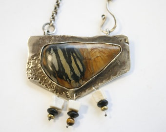 Varigated petrified agate pendant backed on hammered silver  Melinda Salazar