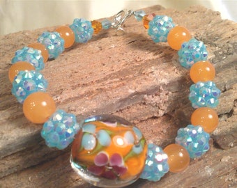 Orange adventurine gemstones and acrylic ab aqua disco ball spacers are highlighted by this beautiful floral handmade lampworks focal bead.