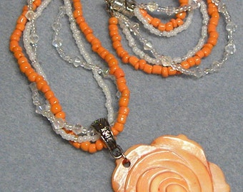 Necklace: Peach Colored Flower on an Orange and Clear Beaded Necklace