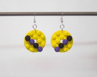 Yellow disk earrings with purple and black pieces and silver plated ear wires