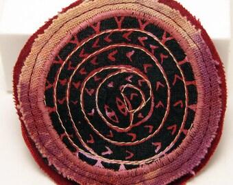 Fiber art brooch pin, fabric brooch, spiral snake design, hand dyed fabric, screenprinted dusty pink, black
