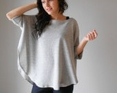 Poncho. Curved hem. Cuffed sleeve. Oversized sweater.