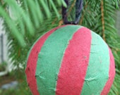 Striped globe ornament made from red and green handmade paper