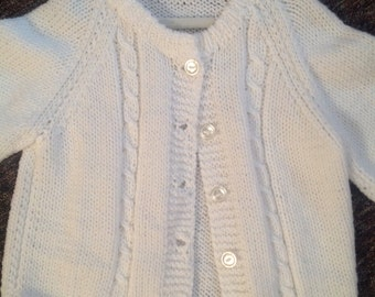 Knitted white child cardigan sweater