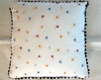Embroidered calico cushion with black pom pom edging