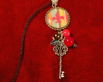 Pink Fleur De Lis Resin charm necklace embellished with a key charm and beads