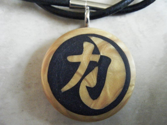 japanese kanji symbol Strength yin yang hand carved on a polymer clay light gold color background. Comes with a FREE 3mm necklace