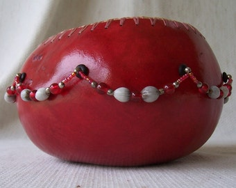Medium bright red gourd bowl, seed and bead swags all around middle. 764.