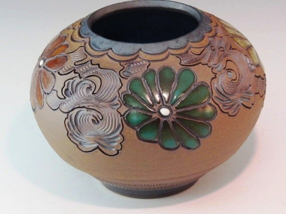 Round Vase With Flowers Carved Around The  Pot