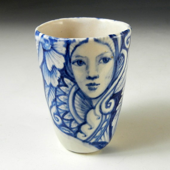 Blue and white hand painted porcelain cup with faces