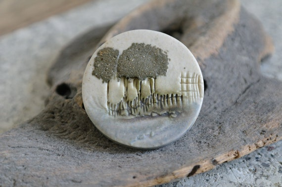 Ceramic brooch with woodland scene.