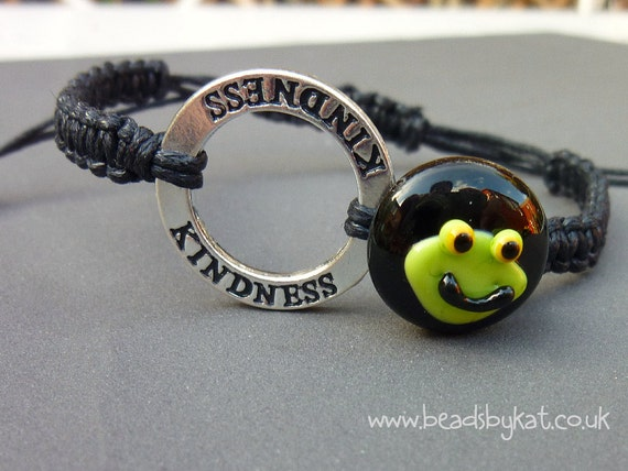 This is a little black button with a frog's face on it, for Team Jaxon F.R.O.G, on macrame'd cotton. The silver coloured affirmation ring says 'Kindness' which is what this is all about