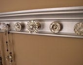 jewelry/ necklace holder with 9 decorative knobs metallic silver finish background  and stunning rhinestone center 26 inches