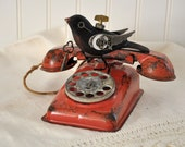 Steampunk  sculpture bird mounted on a vintage childrens red telephone
