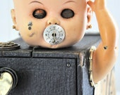Spooky baby doll embellished with vintage items.
