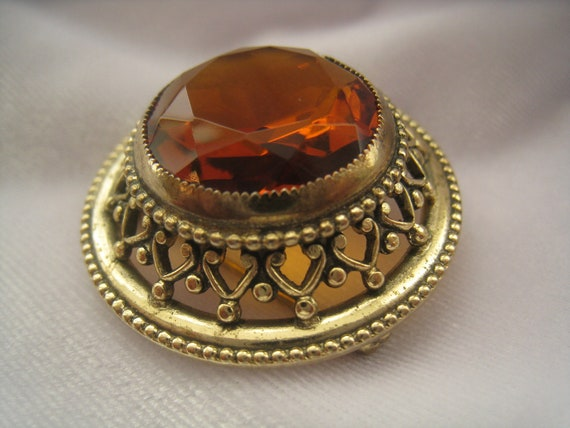 "Vintage Topaz (glass) Solitaire Brooch is bezel set with filigree border and solid  gold tone perimeter is almost 1.5"" across"
