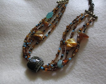 Beaded necklace in warm earth tones.