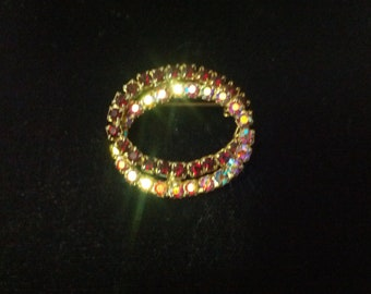 Vintage brooch featuring aurora borellis with bright red rhinestones in a gold tone setting