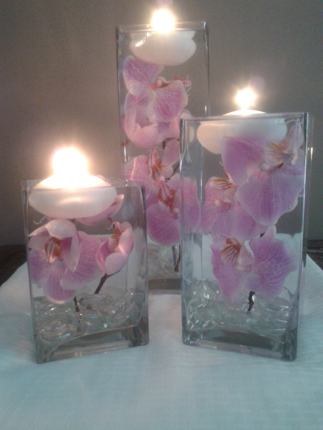 A Set Of Three Square Vases With Purple Orchids Floating In