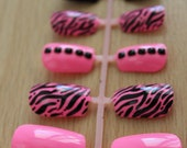 Hot Pink and Black Zebra Nails with Various Designs on a Fake Nail Set