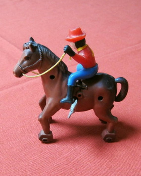 Plastic Wind Up Toy Western Cowboy on Horse With Wheels