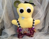 Monster Plush Stuffed Toy: Yellow & Purple with Suspenders and Floral Skirt