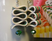 Red, green, and white ribbon candy earrings made of polymer clay with a green dangle.