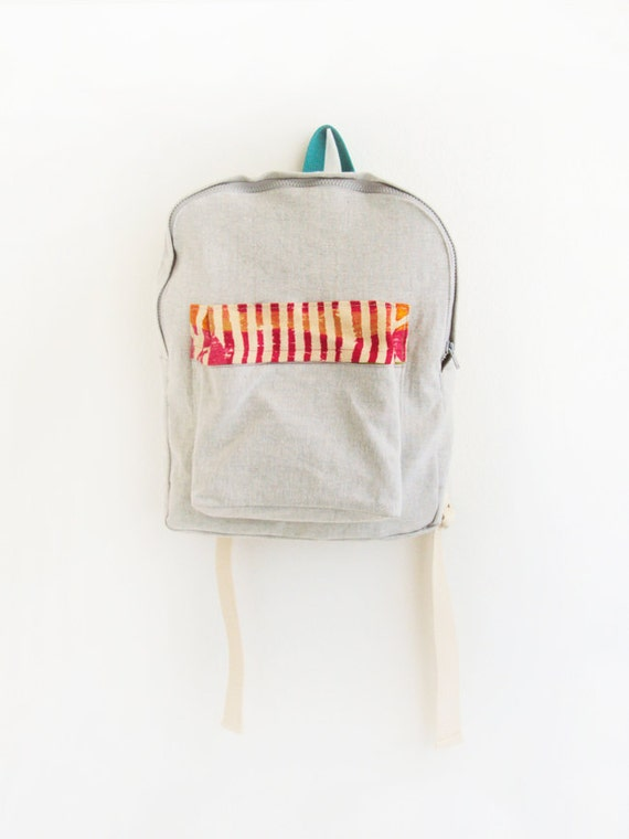 light grey denim backpack with pink and orange pouch