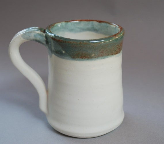 1 white mug with a green and brown decorated rim