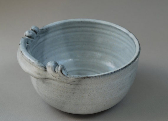 A serving bowl in a white glaze on a rich dark brown clay.