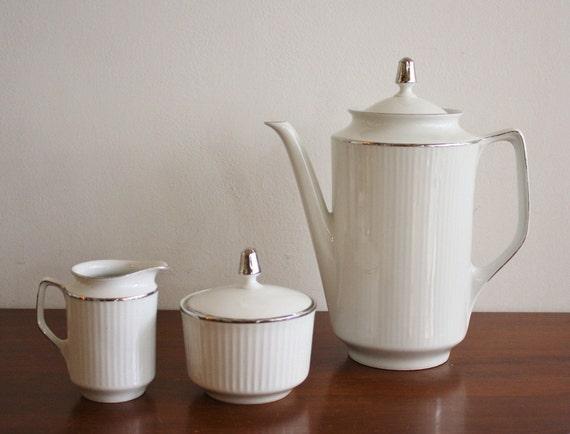White porcelain tea set includes tea pot, sugar and creamer