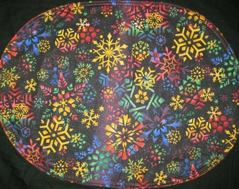 Oval placemats with bright snow flakes on black with  stylized leaves on the back reversible, set of 4