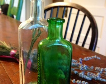 Set of 2 antique glass bottles - one clear and one marked Moone and Emerald Oil